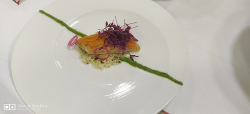 Cod fish with sweet potato scale with mint couscous , Aragula pesto and pickled onion .