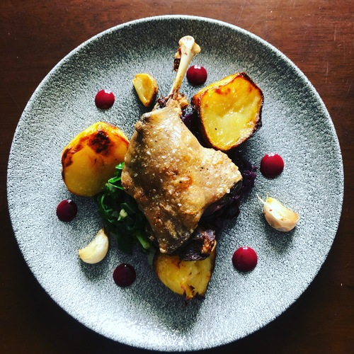 Confit duck leg, duck fat roast potatoes, confit garlic, rainbow chard, braised red cabbage, cherry reduction