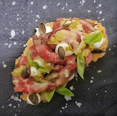 Bruschetta with marinated beef tenderloin,feta cheese mousse,pickled cucumber and pumpkin seeds.
