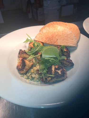 Mediterranean chicken salad pan fried Moroccan spiced chicken chunks with a hot bulgur wheat courgette peppers raisin chick pea and herb salad with mint yogurt and sour dough pitta bread