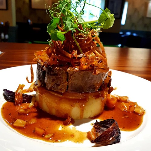Braised beef with rosemary and parmesan mash served with crispy carrots and pasnipsand slow roasted red onions