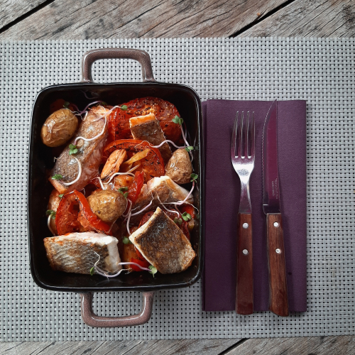 A fish pan with salmon, sea bass and mussels with roasted tomatoes and tasty vegetables