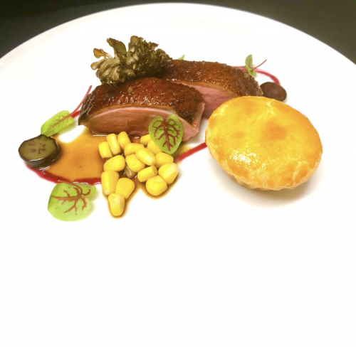Maple glazed roast duck breast and with its duck leg tortiere pie, hen-of-woods mushroom, corn, blueberry gastrique, duck jus