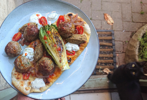 Parsley, Lemon & Cumin Lamb Koftas, Olive & Pepper Tapenade, Charred Baby Gem, Slow Roasted Tomatoes, Picked Red Onion, Tzatziki, Chilli Oil, Rosemary Salted Flatbread, Forgotten Feta, Bonus Cat.  Www.instagram.com/gandalf_the_bearded_one
