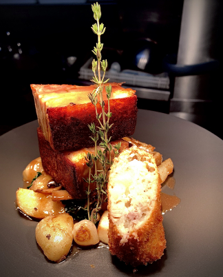 Confit Pork Belly, Braised Savoy cabbage, Baby onions, wild mushroom and jersey royals with a pork and apple Crockette.