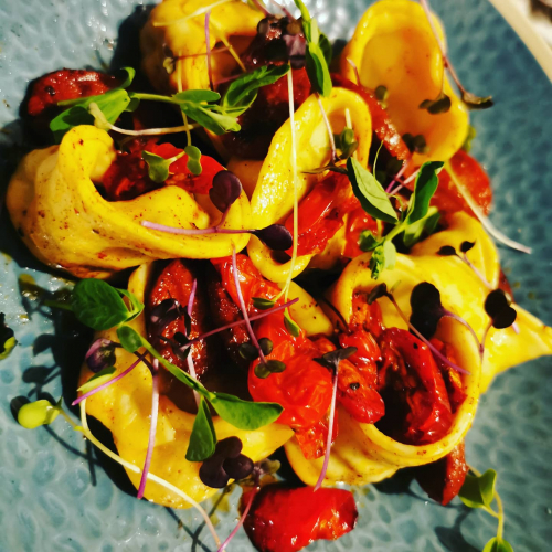 Homemade tortellinis with chorizo,tomatos,butter and a mixed micro herb salad