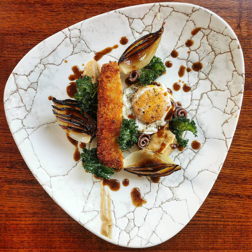 """Pork Holstien""   Crispy pork steak, fried egg, balsamic roast onions, parsnip puree, kale crisp anchovy and bacon jus."