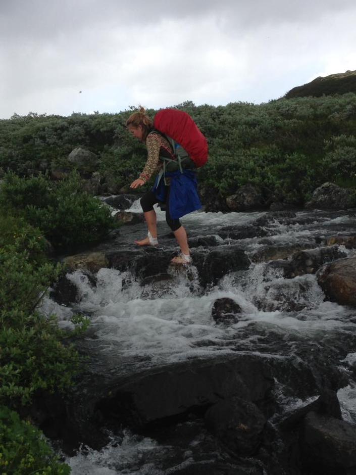 Hege Myklebust i fin stil over ei elv..og fann det lurast å ta av seg skoa. Ho kom dermed over tørrskodd!