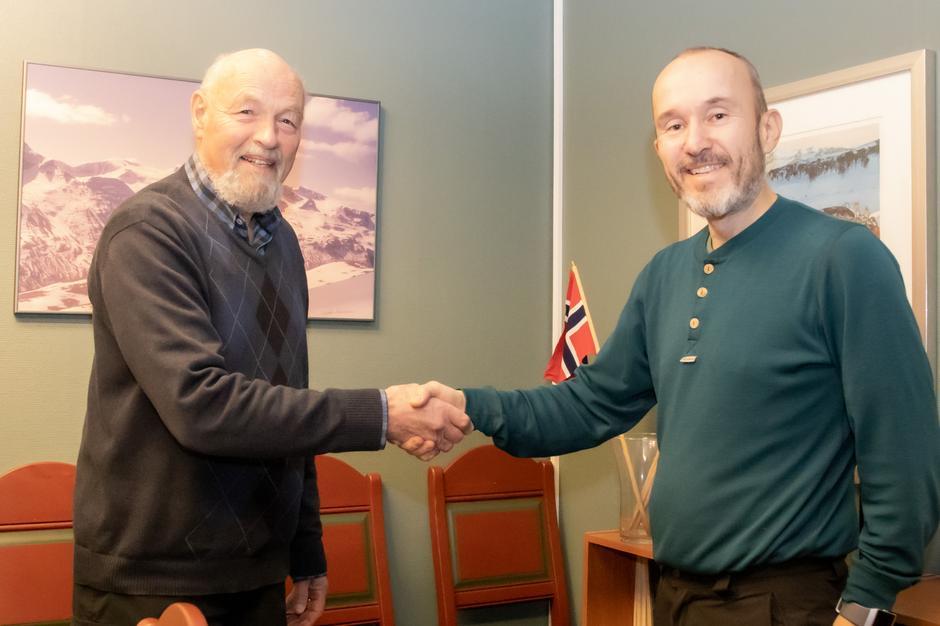 Styreleder Eirik Gudmundsen i Kristiansund og Nordmøre Turistforening gratulerer ny daglig leder Roar Halten med tilsettingen.