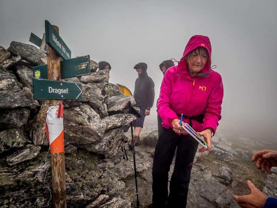 Grethe Johnsen skriver seg i boka på toppen av Saksa i Halsa.