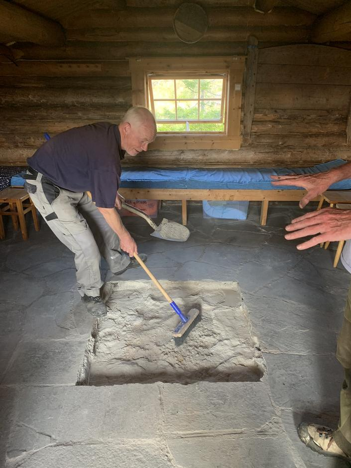 """I koia har vi fjernet ovn og """"mur/grue"""" og den store hetta over. Ole Anders Tomter klargjør for ny koieovn."""