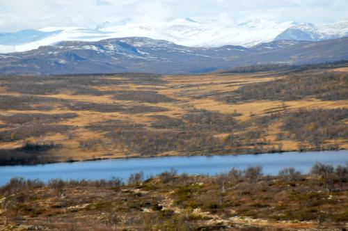 DNT hytta Storkvelvbu.I bakgrunnen Jotunheimen med Rasletind, Mugna, Store Knutsholstind, Leirungtinder, Tjønnholstind og Høgdebrotet.