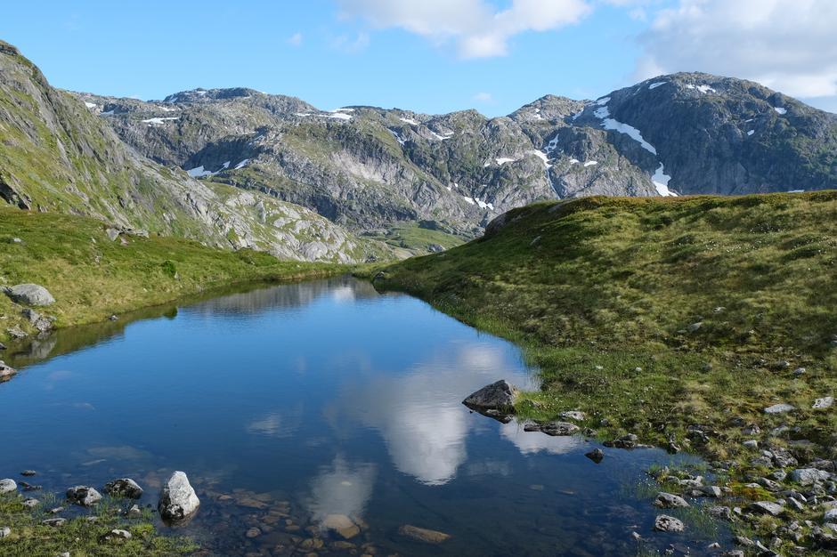 Fagre fjell og himmel som speglar seg i stille vatn.