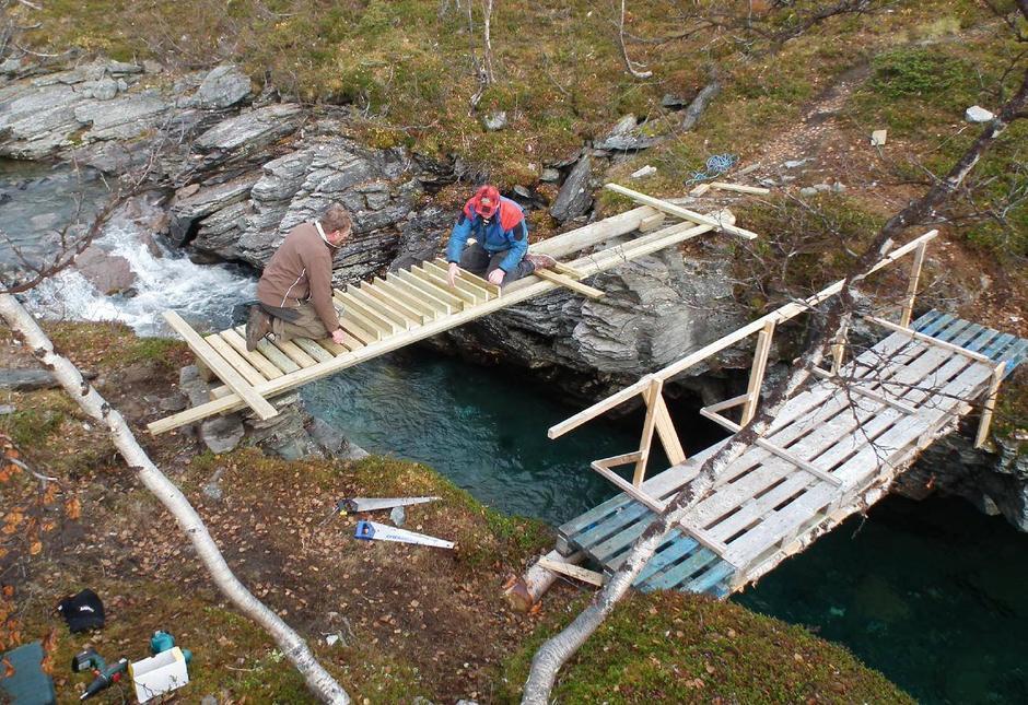 Her er ny bru over Gaskasjohka (Fiskløyselva) under bygging 2. oktober 2010. Nødbrua ses til høyre. Det er Magnar Uvsløkk og Odd Henry Olsen som er ute på brua.