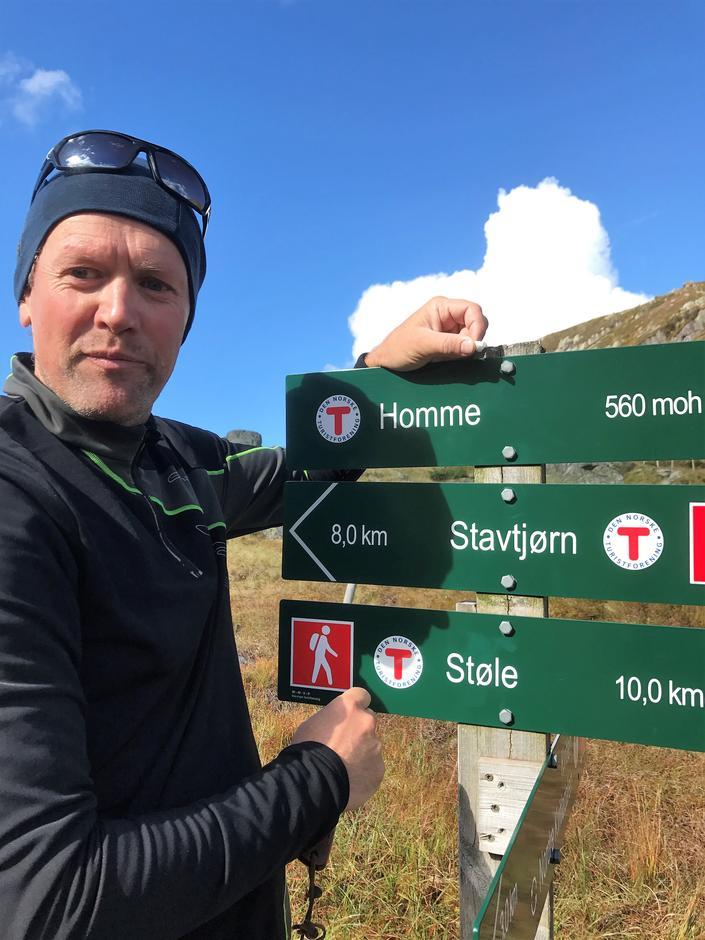 Driftsleder Per Henriksen i STF viser fram de nye metallskiltene.