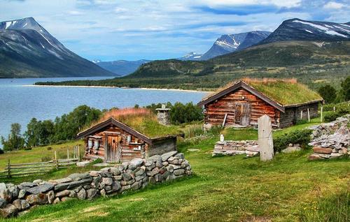 To gamle sæterbygg i tømmer er i fremgrunnen. Rundt er det grønt gress, blå himmel, og fjell.