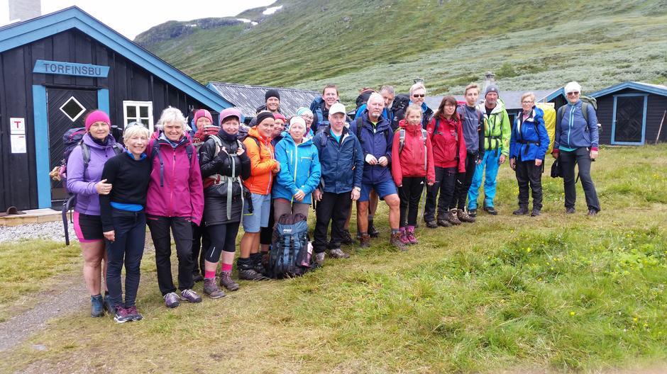 22 godt nøgde turdeltakarar. Mariann Svingen lengst til venstre og ho og Kjell Kleiven leia gruppa gjennom hjarte av Jotunheimen.