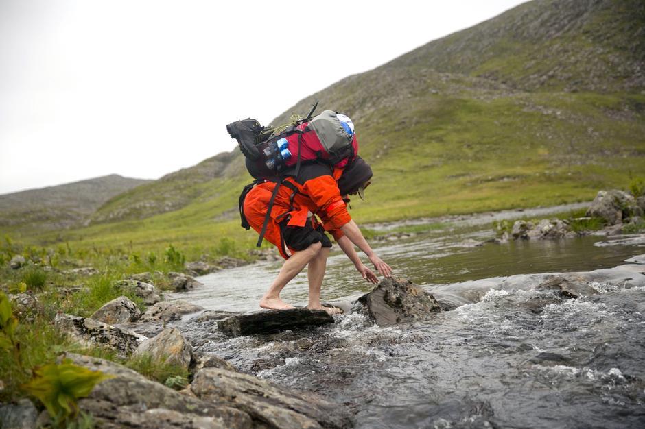Med øl, fiskestang, kokekar og tungt telt i sekken er det ikke helt lett å krysse elva på alle fire. Kaldt er det også.