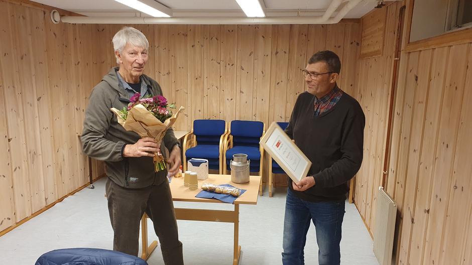 Per Stubbraaten overrekker diplom, merke og blomster til Alf Elling Omholt.