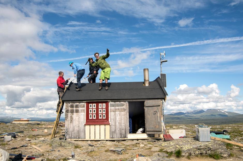 GODT I GANG: Stemningen er skyhøy når gjengen jobber med taket på nødbua Fiskåhøgda.