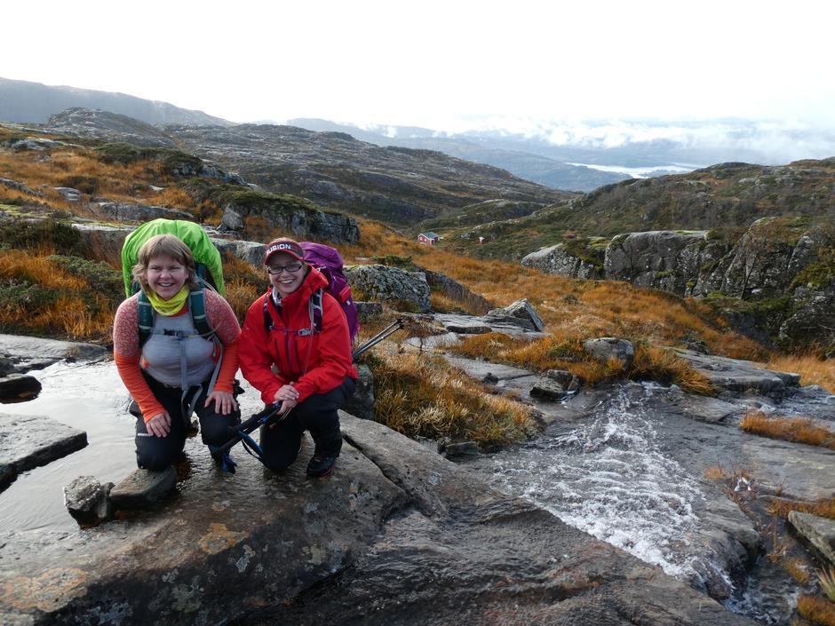 Solfrid og Astrid med haustleg fjell, Nilsebu og Austfjorden i bakgrunnen.