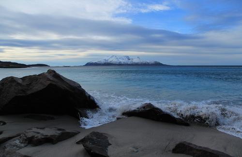Bølger som slår mot stranden med Landegode i bakgrunnen.