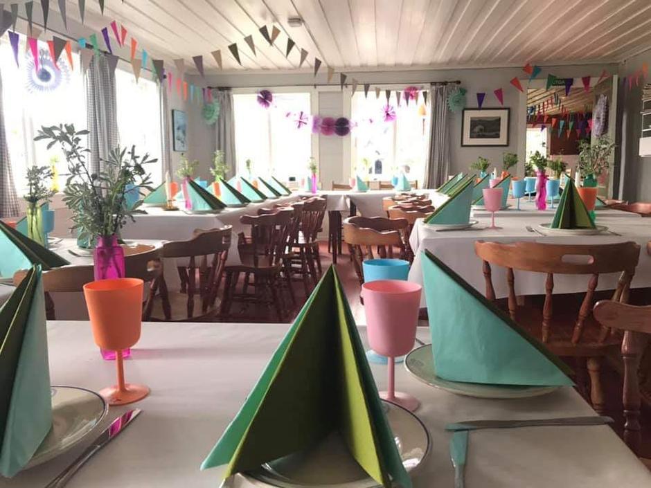 Bordene inne i Sandsa turisthytte er pyntet og klare før den store bryllupsfesten.