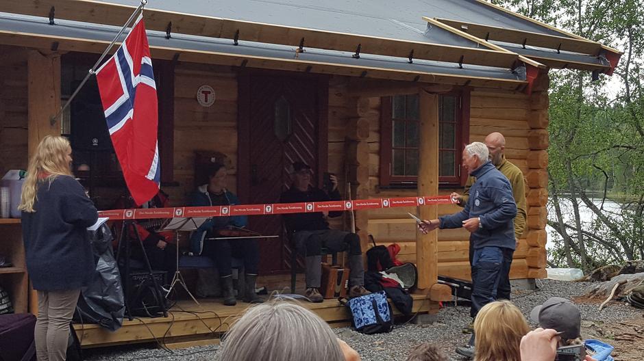 """Et av fjorårets høydepunkter, åpningen av Hovinkoia 12. august 2018. Kjetil Sudgarden klipper """"snora"""" som holdes av Maria og Tom-Erik Bakkely Aasheim."""