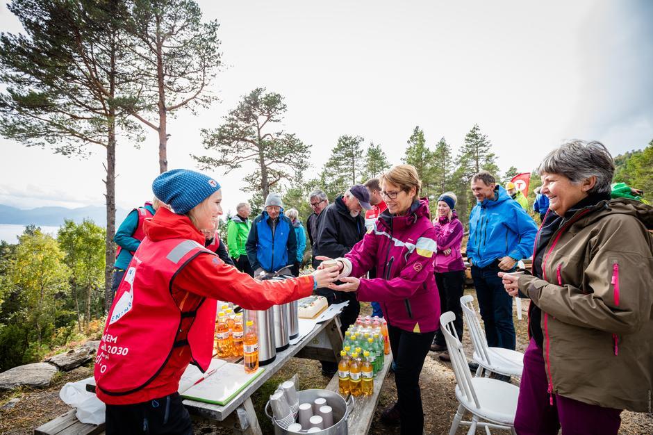 Frivillige hytteverter, Janne og Mari, får kake og kaffe av Maria Holo Leikarnes.