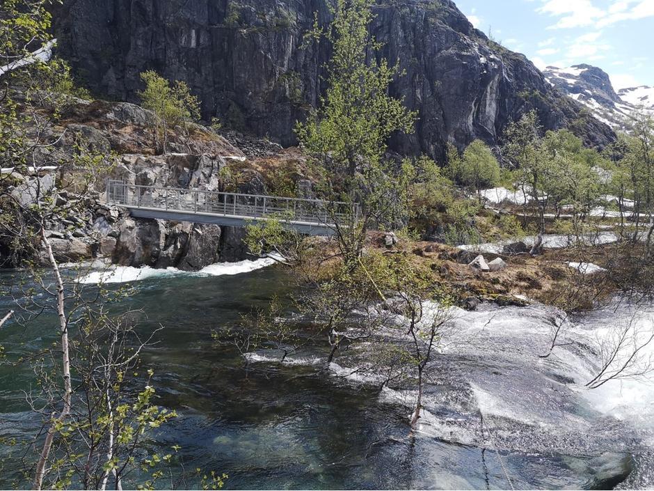 Høy vannføring i Kvanndalsåna. Elva renner over sine bredder før broen, og det er ikke forsvarlig å krysse til der broen er. Det er med andre ord ikke mulig å gå mellom Kvanndalen og Holmavatn, per 14.06.2020.
