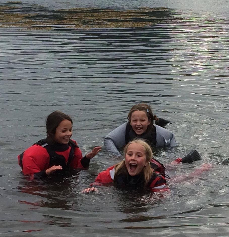 Glade jenter fikk lov til å bade i tørrdraktene når padleøkta var over. Sofie, Silje og Felin viser tydelig at det ble satt pris på!
