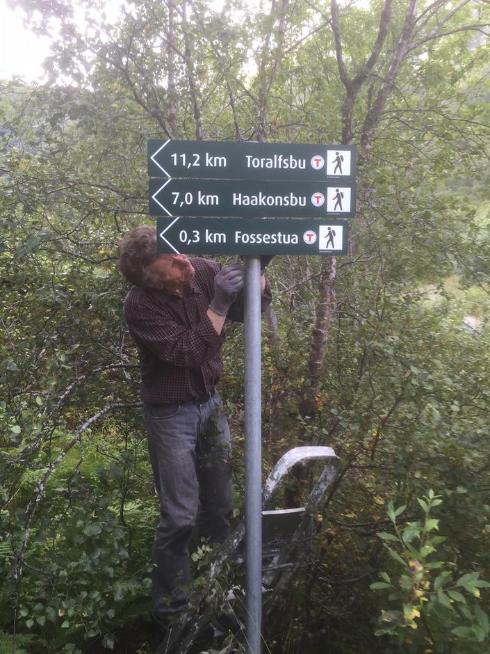 Karl W. Hind monterer nye skilt i Austerfjorden der løypa til Fossestua, Haakonsbu og Toralvsbu starter.