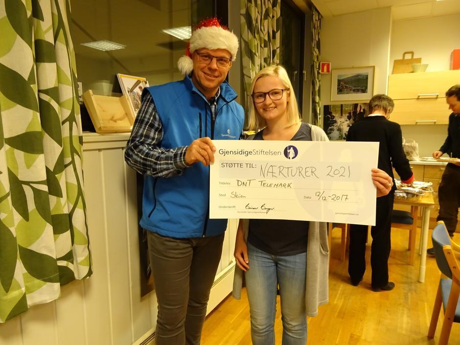 Nils-Magne Myhra fra Gjensidigestiftelsen overrasket Elisabeth Fleseland i DNT Telemark med tilskuddet på 1,1 millioner.
