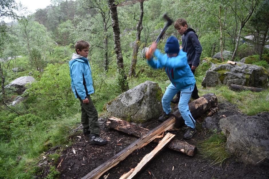 VEDKLØYVING: Med stødige bein svinger Vilde øksa mens Mikkel og Emil venter på sine fem hugg hver.