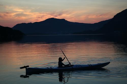 Solnedgang i Botneparadiset. Natalie som koser seg ute i vannet i en kajakk.