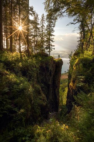 Dette bildet ble tatt omtrent 500 m ovenfor Steinsfjorden, Buskerud, en fin sommerkveld. Den korteste turen opp til Mørkgonga er veldig bratt, men stedet og utsikten er nydelige! Planlegging og været som samarbeidet ga meg lys inni selve Mørkgonga og gjennom trærne. Ved å bruke selvutløseren, forsinket, kunne jeg gå inni ramma for å vise størrelsen av kløften. Jeg synes dette bildet viser godt hvor liten vi er, og bør være, i naturen.