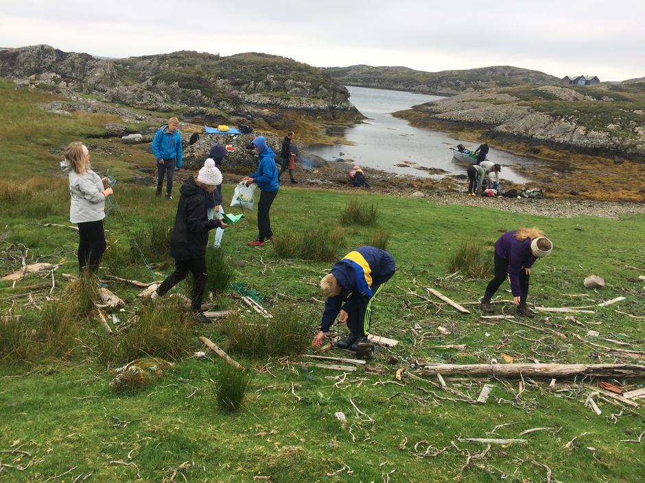Ungdommar plukkar søppel på ei strand innanfor naturreservatet på Værlandet i Soknevågen.