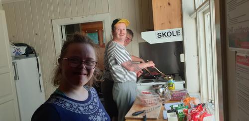 to blide ungdommer som smiler bredt under kjøkkentjeneste på Gaudland