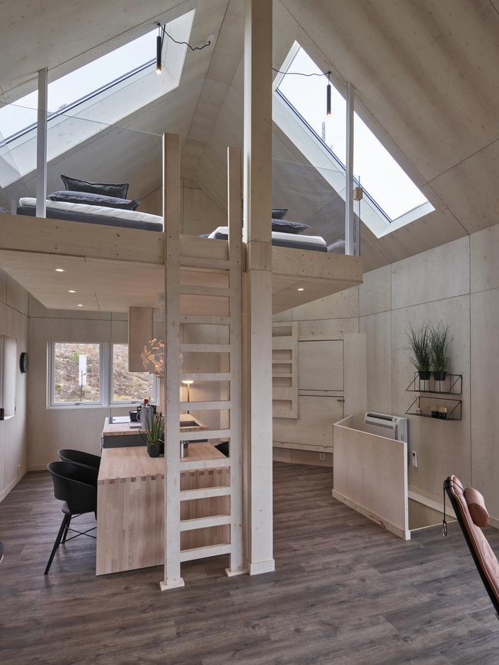 Fra sittegruppen og innover hytta ser man godt den flotte kjøkkenbenken, køyesenga og den flyvende hemsen.