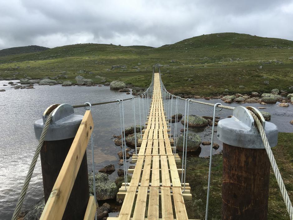 På broa fra Bossbu-siden. Lemmene er 60 cm brede og ligger stabilt inntil hverandre. Solide vaiere å holde fast i ved gange.