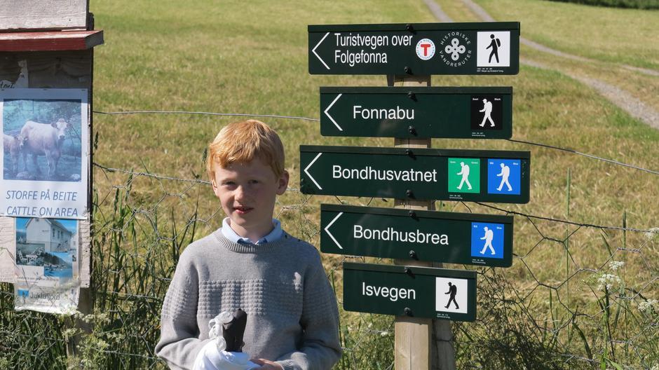 Emil Gausvik (8 år) skrudde opp det nye skiltet for Turistvegen over Folgefonna som historisk vandrerute.