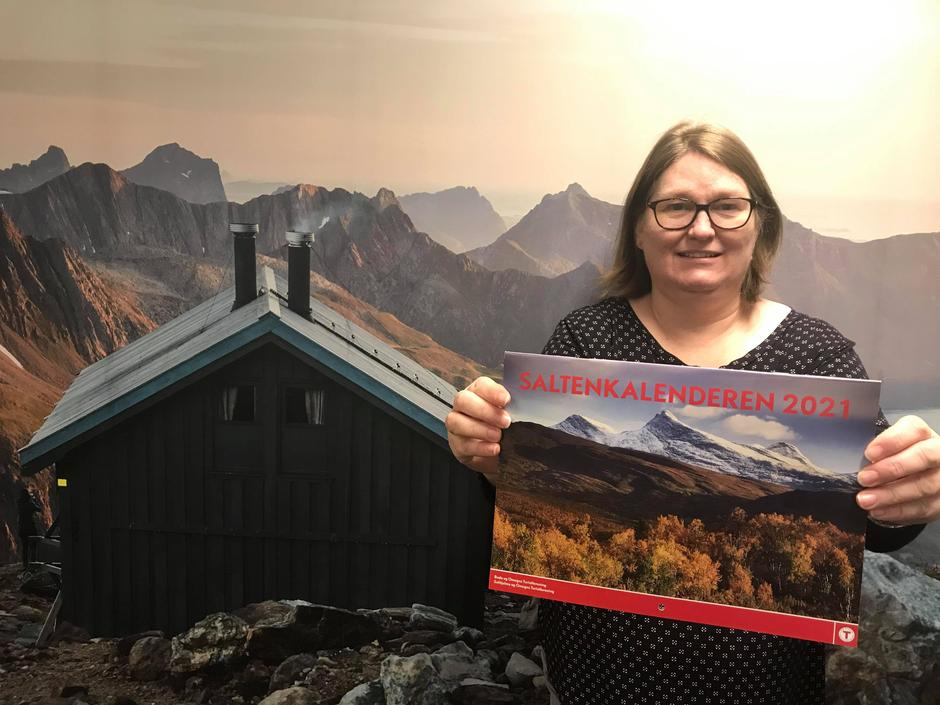 Kari med den nye kalenderen foran vår nye stolthet - bildeveggen av Tåkeheimen.