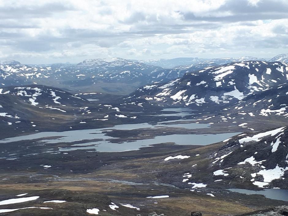 Frå vest på Skamdalshøgda, utsikt over Grindafletvatni og hyttene.
