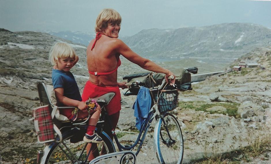 Mor og dotter på sykkeltur på Rallarvegen retning Hallingskeid sommaren 1981. Det var annan trend då med tregirs sykkel og ingen hjelm på verken vaksene eller born.Innsendar av biletet er meg, Heidi Reisegg Endal, som sit bak på sykkelen. Det er min far Richard Jacobsen som har teke biletet. Sykkelen fekk mor mi i konfirmasjonsgåve i 1962. På den tida var det eksklusivt å ha sykkel med tre gir.