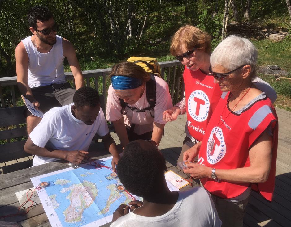 Kurslederne Inger, Randi og Torunn viser hvordan man bruker kompass og leser kart.