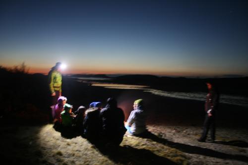 Kveldsmattur med hodelykt, bål og solnedgang..