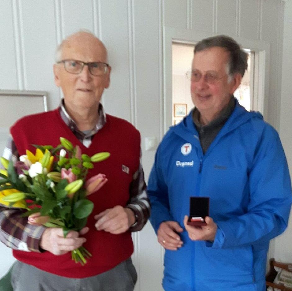 Styremedlem og sambygding Ove Bach overrakte Valter Tinderholt hedersknappen og blomster dagen etter utnevnelsen.