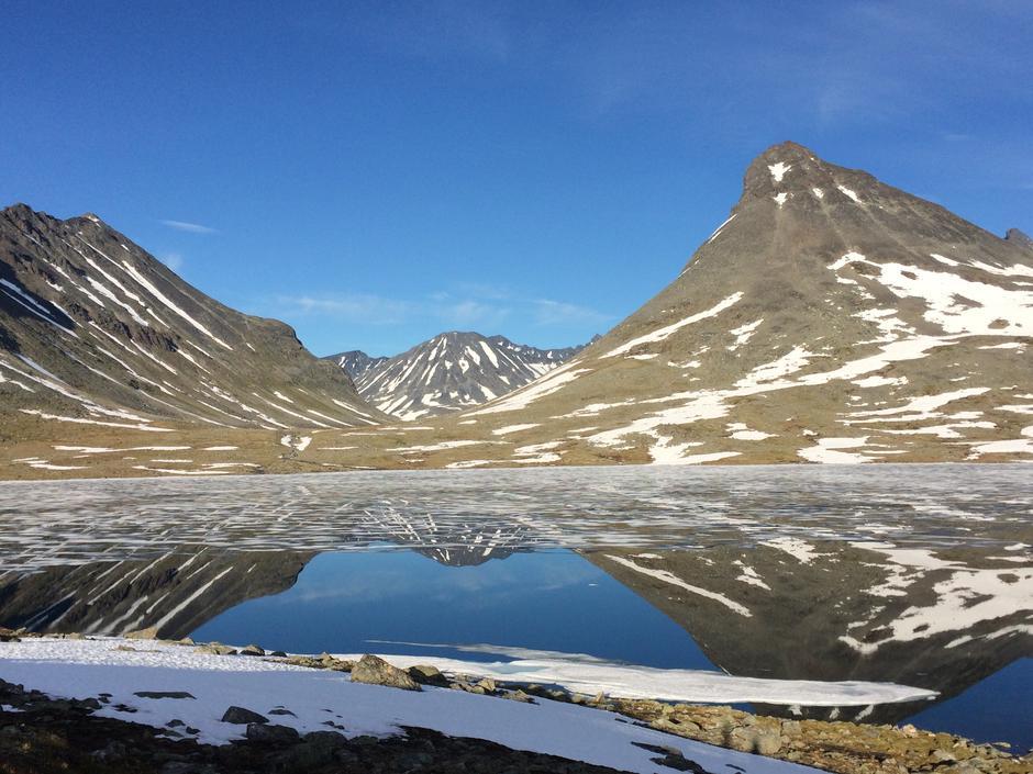 Kyrkja, til høgre, speglar seg på eit islagt vatn ved Leirvassbu.