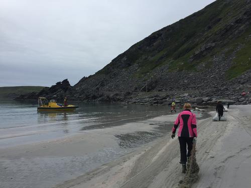 Søppel dras langs stranden for henting av Kystverket