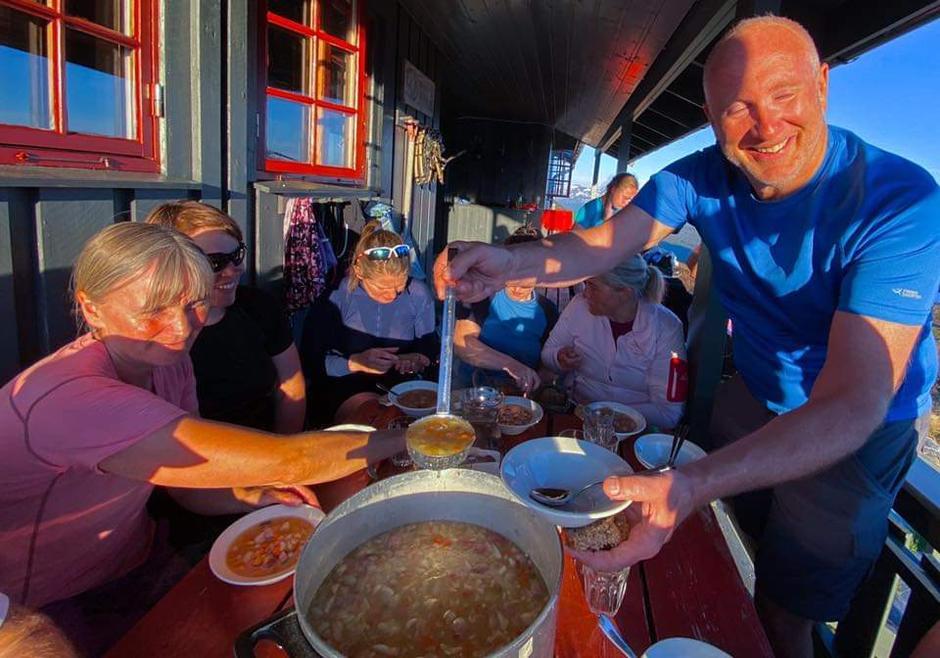 Turleder Birger serverer mat til turfølget.
